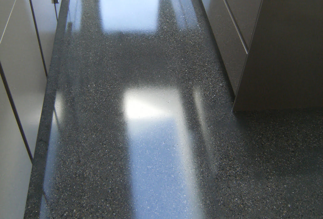 Polished concrete floor coated with a topical seal