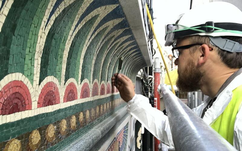 Arbeiter bei der Restaurierung des Mosaiks an der Fassade von Bewley's